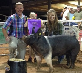Samantha Matthews, Class 1 Hampshire Division, of the Artesia FFA proudly poses with her Grand Champion Swine on Tuesday night at the Eddy County Fair, along with Judge Greg Zedeker of East Liberty Ohio. Zedeker has 23 years judging experience and enjoyed working with the Eddy County youth. Also pictured: Brooklynne Ivans. Liana Swarengin-Artesia Daily Press