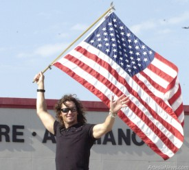 Dave Bray, lead singer of Madison Rising, waves an American flag from the back of the band's float in Thursday's parade. The group performed a free concert for an enthusiastic crowd Thursday evening at Jaycee Park. Brienne Green - Daily Press