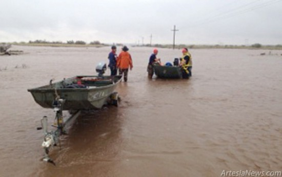 Heavy rains in the Artesia area, falling steadily since Tuesday afternoon, have led to flooding in several locations around Eddy and Chaves Counties. Crews with the Artesia Fire Department, the FLETC and other organizations began evacuating approximately 60 residents from the SKP RV Camp near Lakewood this morning by boat and helicopter. The evacuees were bused to the Artesia Center, which is serving as a shelter at which people forced to leave their residences may obtain food and water. Pictured at left, rescue workers prepare to cross the floodwaters to the campground. In addition, a crew was reported to be waiting on a train stranded on the tracks in the Lakewood area due to floodwaters, and two people were rescued from a flooded vehicle near the Pecos River. The National Weather Service regional office in Midland, Texas, reported flows in Rocky Arroyo near Carlsbad moving close to 12,000 cubic feet per second. Near Hagerman, the Felix River bed was reported to be running bank to bank, as was the Berrendo River bed in Roswell, prompting numerous motorists to stop along the roadway to view a sight residents say they have not seen in decades. More isolated thunderstorms have been forecast for the remainder of today, with rains moving off Friday. Photo Courtesy Leo Sandman