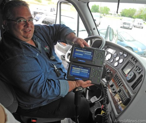 Grace Miller - Daily Press Marvin Baum holds the TransComm and QuailComm systems that communicate with the DOT Command Center to show drivers' time on the road and schedules.