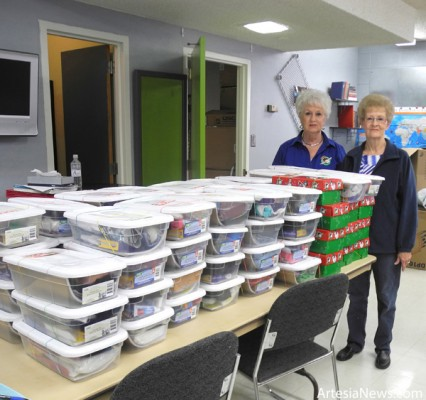 Ruth Bratcher, left, and Anita Lynch, co-chairmen of Artesia's Operation Christmas Child effort, stand with some of the boxes already packed for this year's event. Grace Miller - Daily Press