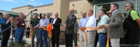 Surrounded by CVE staff and members of the Artesia Chamber of Commerce and Artesia Trailblazers, CVEGeneral Manager Chuck Pinson cuts the ribbon in front of the cooperative's new headquarters this morning. Grace Miller - Daily Press