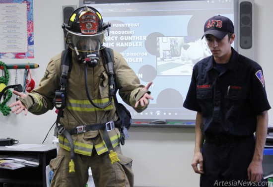 Brandon Messick - Daily Press Firemen Brenden Harvey, right, and Drake Ciacco show D'Mar Ortega's first-grade class at Yeso Elementary School what a firefighter looks and sounds like while wearing his or her gear this morning.