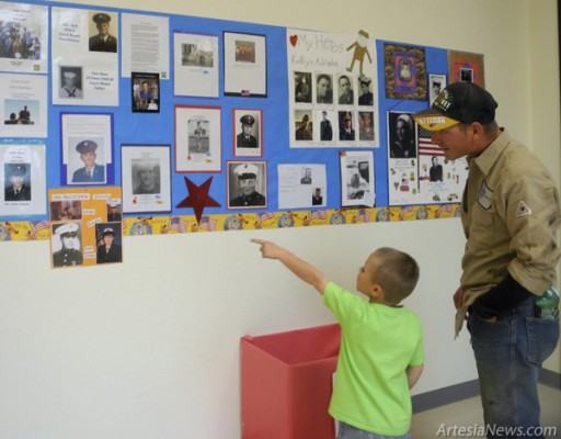 Hunter Ryneer of the Hippo class looks at a photo of his father, Chris Smith, Friday on the Veterans' Day display at Grand Heights. Liana Swarengin - Daily Press