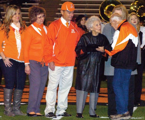Above, Artesia Public Schools Board of Education President Lowell Irby, far right, presents Fid Henderson, widow of late Artesia High School football coaching legend L.G. Henderson, with a plaque commemorating the dedication of the field house at Bulldog Bowl as the L.G. Henderson Field House. Also pictured are Artesia High School head football coach and athletic director Cooper Henderson, his wife, Judy, and daughter, Britni. Brienne Green - Daily Press