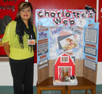 "Roselawn Elementary School third-grade teacher Leslie Catano stands with one of the library book display boards created by students as part of a project for the school's upcoming Reading Fair. In partnership with SD Services, Roselawn will host the fair from 5:30-7:30 p.m. Monday, Nov. 25. ""I want books to come to life for my students,"" said Catano, who organized the reading initiative. ""I want them to get excited about reading!"" Each student was provided a board by SD Services on which they ""broke apart"" a specific book, including criteria such as setting, plot, characters and genre. The ""take home"" project also encouraged parent involvement. The boards will be on display at the Reading Fair. The public is invited to attend. Pizza and drinks will be provided by SD Services. For more information, contact Catano at 746-2812. Courtesy Photo"