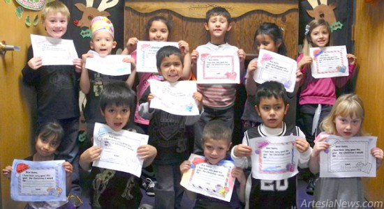 Students in Tracy Allen's Frog class at Grand Heights Early Childhood Center pose in front of the fireplace Thursday with their beautifully colored letters to Santa. The Daily Press is accepting letters through 4 p.m. Wednesday, Dec. 18, which will be passed along to Santa in the Sunday, Dec. 22, edition. Liana Swarengin - Daily Press