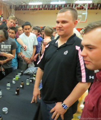 Students at Artesia (Park) Junior High School view a sample of chemicals as Doug Collins with the Navajo Refining Operations Department explains their uses during a Business Day held Tuesday at the school. Several Navajo employees were on hand to give students insight into the various functions of the refinery. Grace Miller - Daily Press