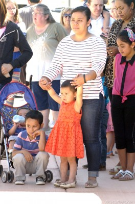 At left, 3-year-old Yaresli Salamanca holds onto her mother, Berenice Salamanca, as she watches performances by Park Junior High School choir students Saturday at the Artesia Public Library, the endpoint of the Boots*to*Fill event organized to benefit Yaresli, who was diagnosed last spring with acute lymphoblastic leukemia (ALL). Artesians contributed used boots and shoes, inscribed with inspirational messages for Yaresli on the soles and containing donations, and attendees of Saturday's event followed the Artesia High School band down Main Street as the footwear was lined up along the sidewalks from The Derrick Floor to the library. Berenice Salamanca was overcome with emotion as she thanked the community for its support of her young daughter as she undergoes regular chemotherapy treatments in Albuquerque. All funds raised through Boots*to*Fill will go directly toward Yaresli's medical bills. The campaign evolved from a children's book authored by event organizer Toni Haas, who expressed her appreciation for the outpouring of donations and well-wishes for the Salamancas.  Brienne Green - Daily Press