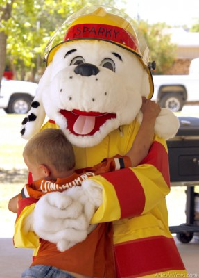 Sparky the Firedog share a hug with a young fan Saturday at the Child Safety Fair at Guadalupe Park.  Brandon  Messick - Daily Press