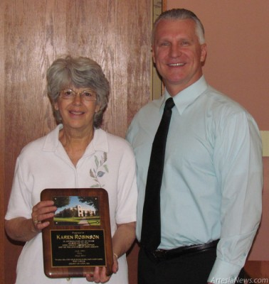 Courtesy Photo County Assessor Karen Robinson is presented with a plaque by County Manager Rick Rudometkin in honor of her retirement.