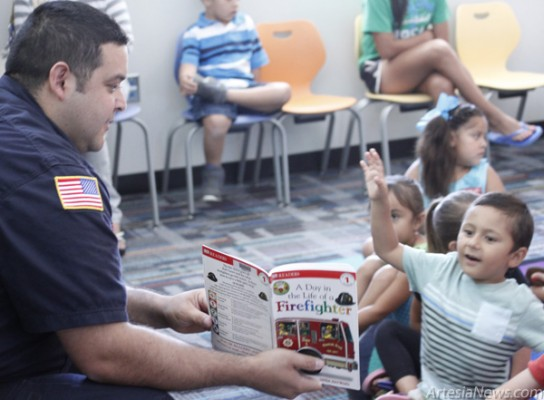 "Firefighter Freddie Florez reads ""A Day in the Life of a Firefighter"" to children this morning during a Fire Safety Fair at the Artesia Public Library. The book and nearly 30 others were donated to the library today by the AFD through a grant from Wal-Mart. Brandon Messick - Daily Press"