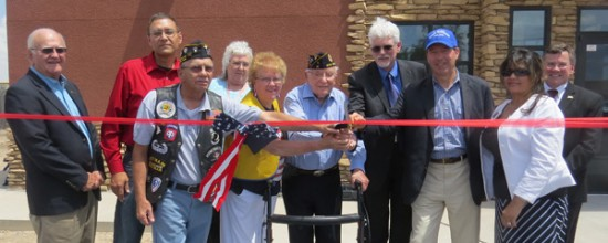 Grace Miller - Daily Press Senator Tom Udall, third from right, joins a group of dignitaries, VAofficials and clinic staff, and World War II veteran John Simmons, center, in cutting a ribbon to signify the opening of Artesia's new VA facility.
