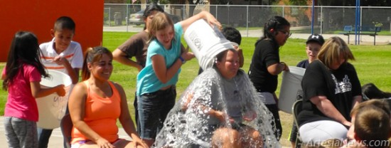 "Above, the playground at Yucca Elementary School was filled with laughter Monday as students dumped buckets of ice water on the heads of teachers. Yucca participated in the Ice Bucket Challenge after two weeks of fundraising for ALS and three local organizations. At left, Yucca Principal Christy Takacs stands with students holding up signs to show the amount of money raised for each charity while ""calling out"" Hermosa Elementary Principal Mike Worley and the Super Kids. Liana Swarengin - Daily Press"