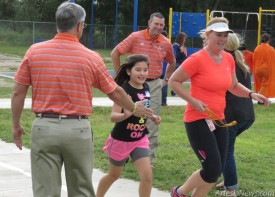 Above, Hermosa Super Kids cheer as they prepare for the school's annual Spirit Run. At left, Artesia Public Schools Superintendent Dr. Crit Caton, left, encourages runners, includ- ing coach Kate DeHoyos, right, and Assistant Superintendent of Curriculum John Ross Null. Grace Miller - Daily Press
