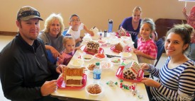 Clockwise from left, Shane Helton, Bayleigh Helton, Karen Helton, Braden Helton, Katie Larsen, Norrie Larsen, Brooklyn Fuentes and Kyla Helton are up to their elbows in gumdrops, pretzels, fluff and candy canes Saturday during the Artesia Arts Council's Gingerbread House Workshop at the Ocotillo Performing Arts Center.  Grace Miller - Daily Press