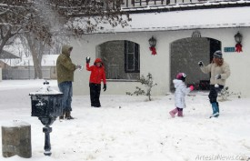 Above, the Maruffo family found the weekend snow to be an entertaining part of their day. From left, Armando, Demi, Ciarra and Colette are sidetracked by a snowball fight while building a snowman in their front yard. For City of Artesia workers, however, the winter storm that created dangerous driving conditions in some areas of town meant busy days plowing and trimming trees that had sunk too close to power lines due to the weight of the snow.  Grace Miller - Daily Press