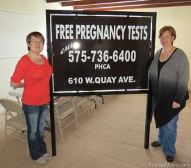 Amanda Ramsey, left, director of the Pregnancy Help Center of Artesia (PHCA), and Arlis Blackwell of Lifeline Children's Services pose with signage to be installed this week at the PHCA's new headquarters at 610 W. Quay Ave.  Grace Miller – Daily Press