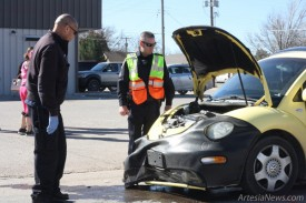 Authorities survey the damage to a yellow Volkswagen Beetle this morning following a collision at the intersection of South 13th Street and West Grand Avenue. According to Artesia Police Department officers on the scene, witnesses stated a green Ford 150 pickup was traveling eastbound on Grand through a green light when the Beetle, traveling south on 13th, failed to stop at a red light and struck the Ford. No injuries were reported. Both vehicles sustained extensive damage to their front ends and had to be transported from the scene. The driver of the Beetle was cited for running a red light.  Ben Theobald – Daily Press