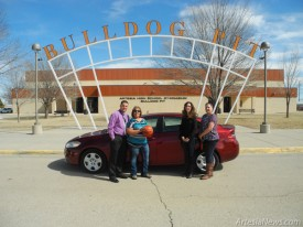 Kandy Molina, holding basketball, stands with Bulldog head basketball coach Michael Mondragon, girls' Booster Club president Shelli Taylor, left, and boys' Booster Club president Christie Harris alongside the new 2015 Dodge Dart Molina won in a recent raffle fundraiser to benefit the Artesia High School basketball programs. The vehicle was purchased by the boosters from Tate Branch Dodge. Friday, Feb. 13, turned out to be Molina's lucky day, as her ticket was drawn from among those sold to both home and visiting fans over the course of several games.  Teresa Lemon - Daily Press