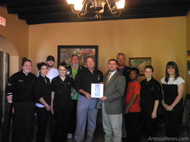 "Adobe Rose Restaurant owner Tom Winters, center left, accepts a designation from Artesia Trailblazers President Jessie Brownfield this morning after Trailblazers and members of the Artesia Chamber of Commerce surprised the local eatery with the Business of the Month award for April. ""I would like to take this opportunity to appreciate the folks that are making the trip around the construction to continue to support the restaurant,"" said Winters. Pictured from left are chef Chloe Winters, Mia Morales, Cody Connor, Amanda Hernandez, David Grousnick, Winters, Brownfield, Perry Troublefield, Kandel Gray, Hope Kraft and Kelcey McCaleb.  Teresa Lemon – Daily Press"