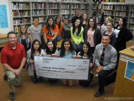 Park Junior High School Principal Cody Skinner, kneeling at right, and librarian Jennifer Duff, second row, second from left, accept a check in the amount of $15,000 from HollyFrontier, presented by Navajo Refining Plant Manager Bob O'Brien, kneeling at left, this morning at the school, joined by several students. HollyFrontier donated $5,000 to the Park library's Funds4Books campaign and $10,000 toward teacher professional development training.   Teresa Lemon - Daily Press