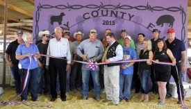 Eddy County Fair Board President John Bain prepares to cut the ceremonial ribbon signifying the start of the 2015 Eddy County Fair Monday afternoon at the fairgrounds as other county fair and Eddy County officials, and members of the Artesia Trailblazers and Artesia Chamber of Commerce look on. Visitors had already begun streaming in by 5 p.m. to view exhibits and sample the fair food, with junior livestock shows also beginning Monday evening. The fair will run through Saturday.  Teresa Lemon - Daily Press
