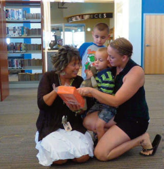 Debbie Bell, left, community affairs administrator with HollyFrontier / Navajo Refining Corp. shows Noah Garcia the new Kindle Fire tablet he won as a grand prize in the Artesia Public Library's summer reading program. With Noah are his brother, Jude Garcia, and mother, Cara Garcia. HollyFrontier and Navajo donated the tablets, which allow users to quickly download books, to the program. (Courtesy Photo)