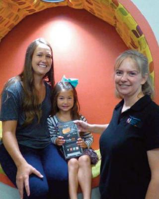 Laura Simon, right, of the Artesia Public Library presents a Kindle Fire to Breckyn Miller. Also pictured is Breckyn's mother, Megan Miller. (Courtesy Photo)