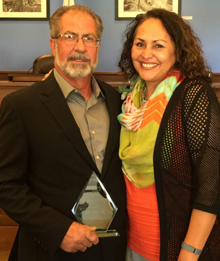 Bill Morton holds his Community Heroes Award from the New Mexico Coalition Against Domestic Violence Sept. 24 in Taos. Also pictured is Celina Bryant, executive director of Grammy's House. (Courtesy Photo)