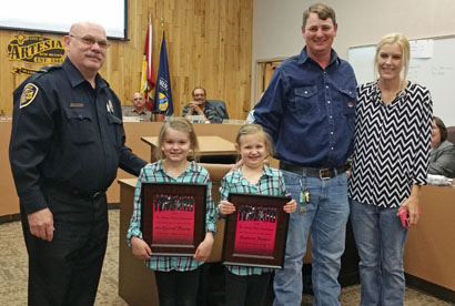 Police Chief Don Raley stands with ArieYannah and Zaphaera Fletcher and their parents, LaShelle and Lane Fletcher, at Tuesday's city council meeting. The girls were awarded plaques by Raley for their Subway gift card donation to the Artesia Police Department. (Courtesy Photo)