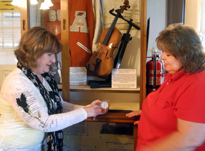 Artesia Historical Museum Manager Nancy Dunn shows the museum's newest employee, Kim Kafton, how to properly use a thermohygrometer, which measures the humidity of a display case. (Elizabeth Lewis - Daily Press)