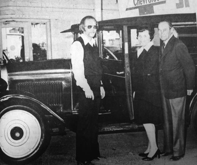 ONE OF THE FIRST - Clyde Guy, right, who today celebrates the 50th anniversary of his association with Guy Chevrolet Company of Artesia, shows his wife, Mary Joe, and son, Eddie, one of the first automobiles he ever sold in the community, a 1928 Chevrolet. The restored antique is only one of more than 35,000 automobiles Guy and his company have sold during the past 50 years. Guy Chevrolet will celebrate the anniversary with a public open house. (Daily Press 1975 File Photo)