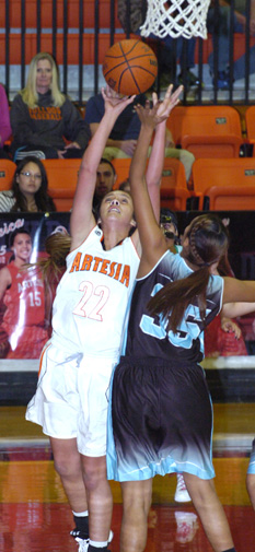 Gracie Puentes puts up a shot under pressure during the second quarter Tuesday at Bulldog Pit. (Brienne Green - Daily Press)