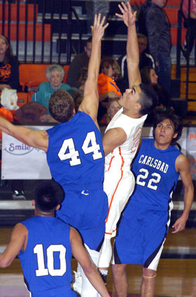 Carlos Carrasco puts one off the glass over Carlsbad's Gage Shoup during the first quarter Tuesday at Bulldog Pit. (Brienne Green - Daily Press)