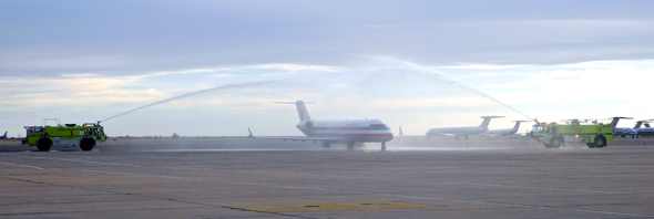 Roswell airport firetrucks create a water cannon salute for the new American Airlines 50-passenger jet as it arrives Thursday afternoon from Phoenix to the Roswell International Air Center. (Elizabeth Lewis - Daily Press)