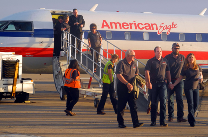 Mayor Phillip Burch, left, chats with Mack Energy Corporation Vice President Chance Chase, second from left, as the two disembark the inaugural American Airlines Phoenix to Roswell flight Thursday in Roswell. (Elizabeth Lewis - Daily Press)