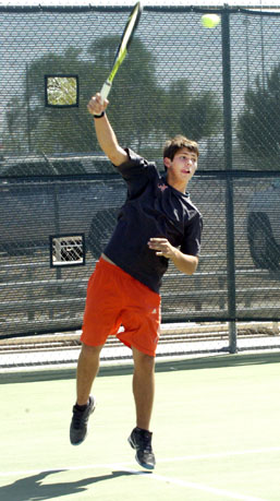 Tailor Baggerly sends a serve over the net in boys' doubles action Monday against Lovington at The Mack. (Brienne Green - Daily Press)