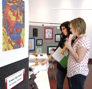 Judges for the Russell Floore Memorial Student Art Show, Artesia MainStreet Executive Director Elisabeth Jackson, left, and Artesia Chamber of Commerce Executive Director Hayley Klein, consider a selection of artwork. (Courtesy Photo)