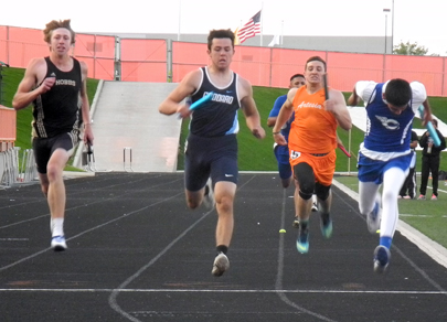 Ethan Duff, second from right, heads for the finish line during the boys' 800-meter relay at Bulldog Bowl. (Teresa Lemon - Daily Press)