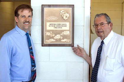 Robbie Burgess, left, and Bob Hendrickson pose with a plaque commemorating 50 years in business with Artesia Ford Sales. (Courtesy Photo)