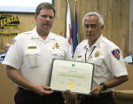 Fire Marshal James Abner, left, receives his Master Code Professional designation from the International Code Council, presented by Fire Chief J.D. Hummingbird during Tuesday's city council meeting. (Elizabeth Lewis - Daily Press)