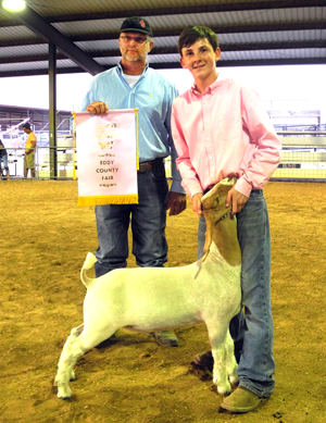 Kaylin Klein of Cottonwood 4-H shows his Reserve Champion meat goat as judge Jimmy Davis of Walter, Okla., holds his banner Wednesday evening at the Eddy County Fair. (Teresa Lemon - Daily Press)