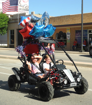 A pair of local children navigate a festively-decorated dune buggie through the Fourth of July Parade Monday morning on Main Street. (Brienne Green - Daily Press)