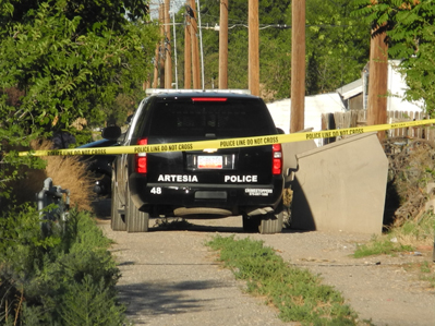 Artesia Police Department officers wait in the alley behind the home on Washington Avenue between 11th and 12th streets this evening as they work to apprehend the suspect, who had barricaded himself inside. (Brienne Green - Daily Press)