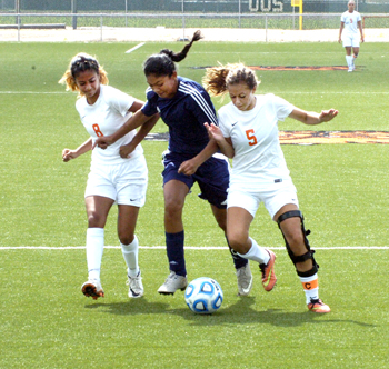 Destiny Gonzales (8) and Jailyn Ruiz (5) battle a Deming forward Saturday. (Brienne Green - Daily Press)
