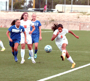 Elisa Cardenas skirts the sideline to send a ball up into Artesia's front third as teammate Ashley Hernes (18) and a pair of Cavegirls look on during the first half of the Lady Bulldogs' 5-0 loss to Carlsbad Tuesday at The Mack. (Brienne Green - Daily Press)