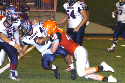 Codey Scott drags down Deming quarterback Cristian Metz. (Brienne Green - Daily Press)
