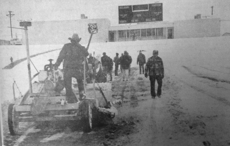 FUTILE EFFORT - Before the cancellation of Saturday's Bulldog-Caveman football game, crews began intensive efforts to clear Bulldog Bowl of about six inches of snow which fell upon Artesia Friday. A large grader and a street sweeper, above, were brought in to help with the operation, which was in vain as the game was eventually cancelled because of Carlsbad's concerns over road conditions. (Daily Press 1976 File Photo)