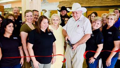Bennie's Western Wear owner Jimmy Mason cuts a ceremonial ribbon at the shop's new location in Carlsbad Monday, surrounded by family, friends, staff and Carlsbad business representatives. (Photo Courtesy Robert Defer)